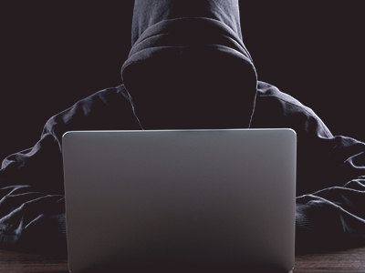hooded figure maliciously using a laptop